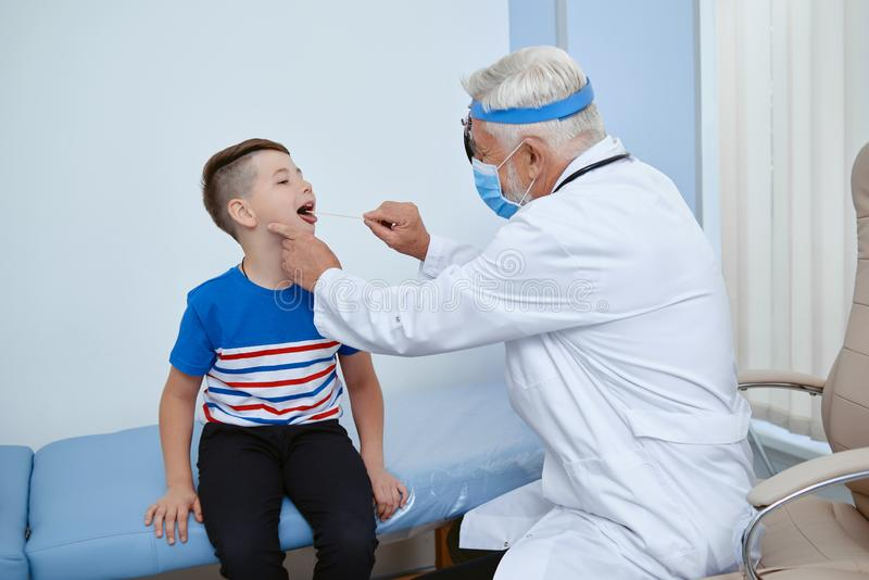 Doctor in uniform in mask treating young patient. royalty free stock image