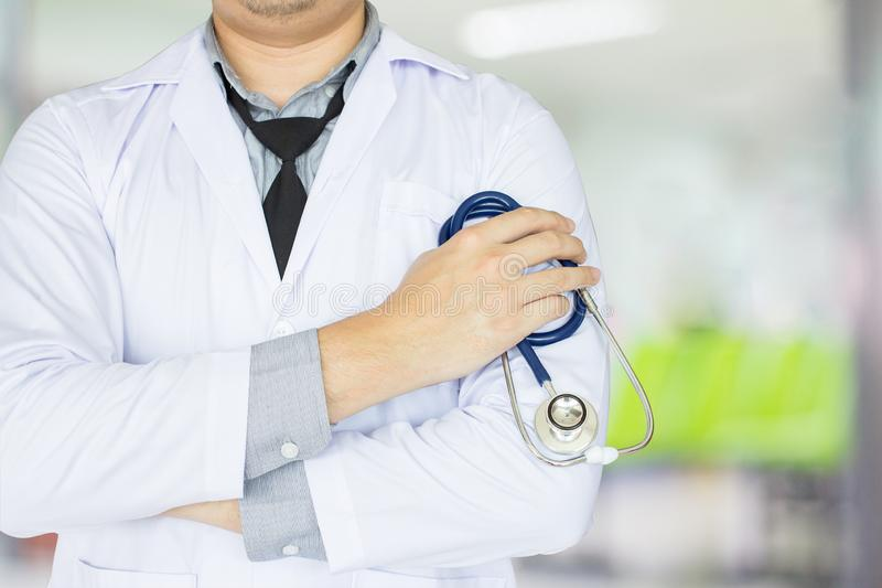 Doctor in uniform standing and holding a stethoscope working at a hospital with a health care royalty free stock photo