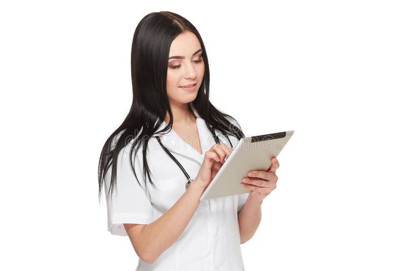 Doctor in uniform using tablet and reading information about patient. stock photos