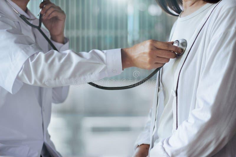 Doctor usando el estetoscopio que comprueba el ritmo cardíaco para saber si hay pacientes mayores en hospital fotografía de archivo libre de regalías