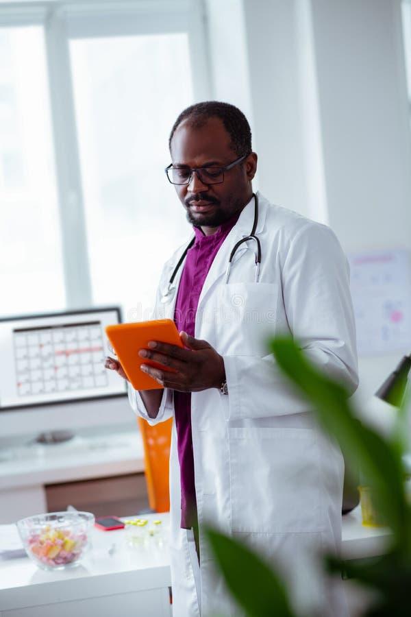 Doctor usando la tableta mientras que busca para una cierta información imágenes de archivo libres de regalías