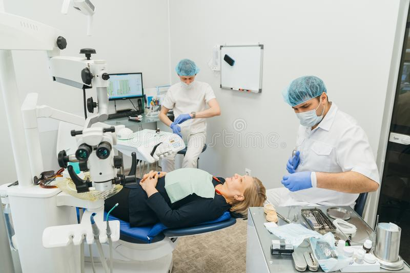 Doctor used microscope. Dentist is treating patient in modern dental office. Operation is carried out using cofferdam. Client is inserted and restored teeth royalty free stock images