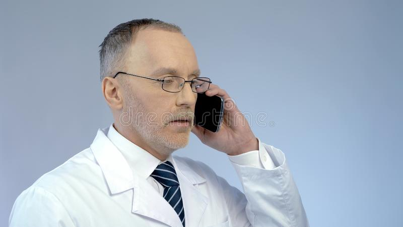 Doctor using cellphone to arrange meeting, remotely monitoring treatment process. Stock photo stock image
