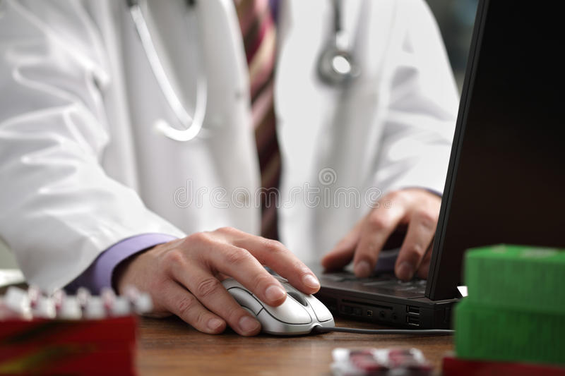 Doctor using computer. Doctor using a laptop computer to prepare an online prescription