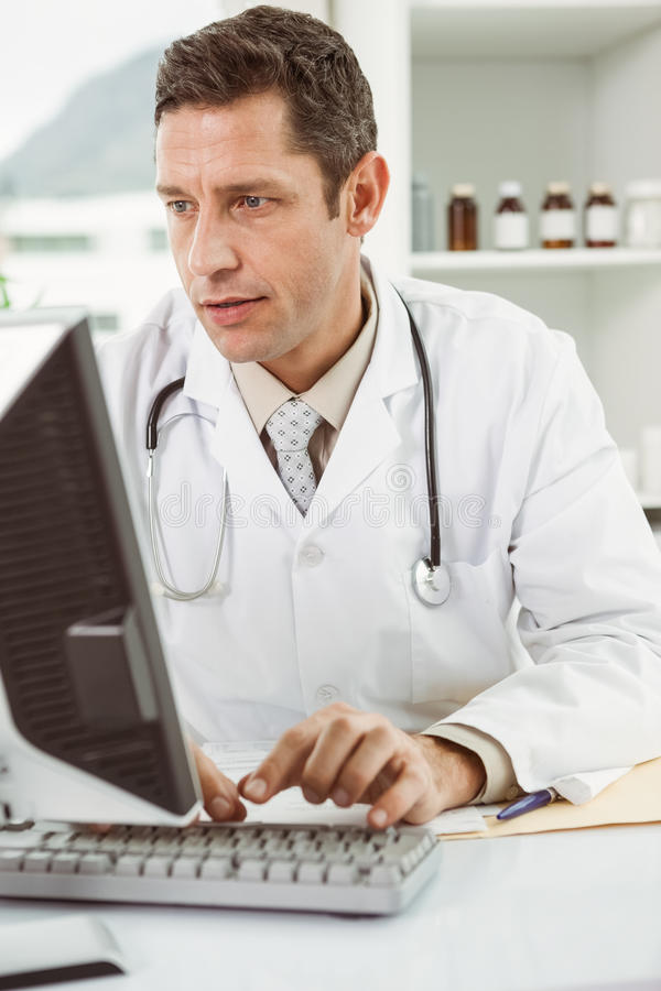 Doctor using computer at medical office stock photography