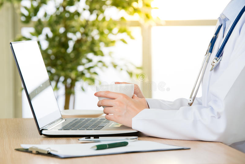Doctor using computer to research internet and drink coffee stock image