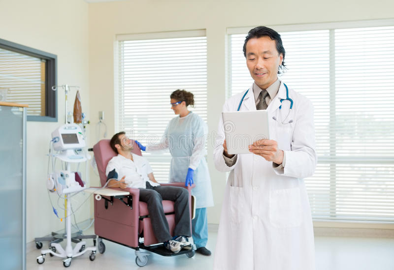 Doctor Using Digital Tablet In Chemo Room stock photos