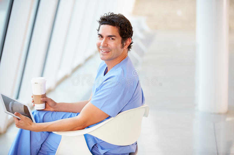 Doctor Using Digital Tablet On Coffee Break In Hospital stock photos