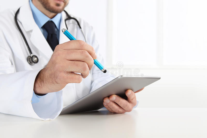 Doctor using digital tablet on desk stock photo