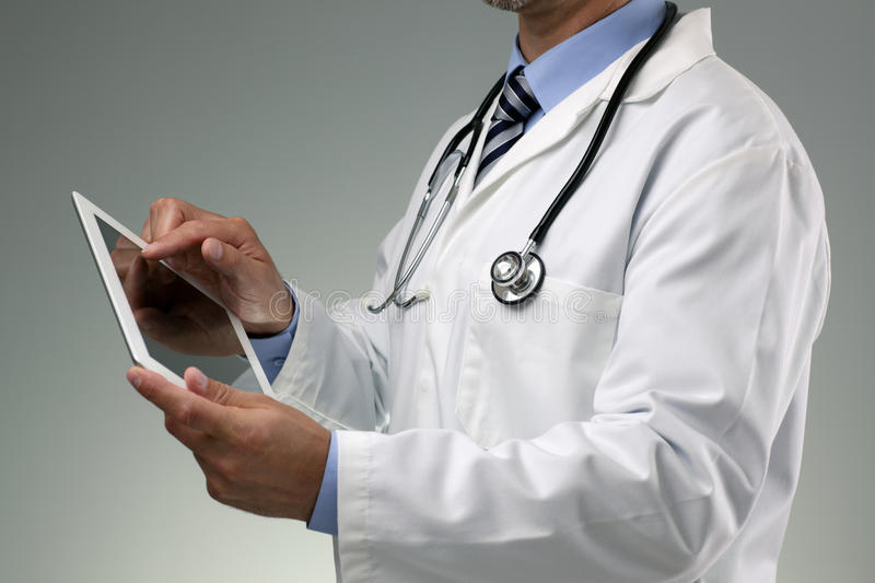 Doctor using digital tablet. On gray background
