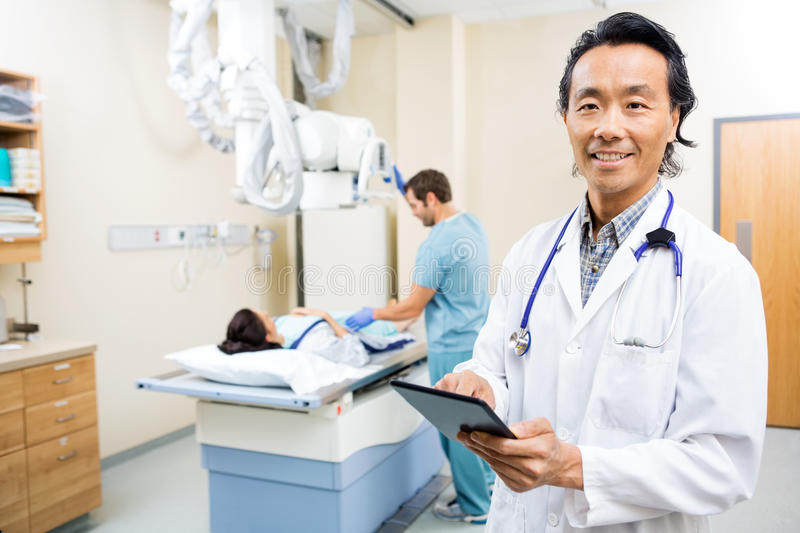 Doctor Using Digital Tablet In Hospital Room. Portrait of male doctor using digital tablet while nurse preparing patient for xray in hospital room stock images