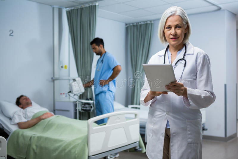 Doctor using digital tablet in ward stock photo