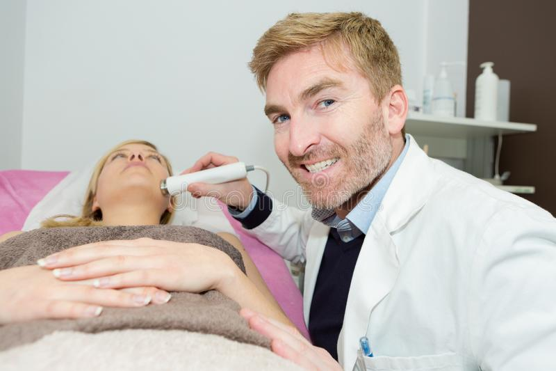 Doctor using electric device on female patients chin royalty free stock photo