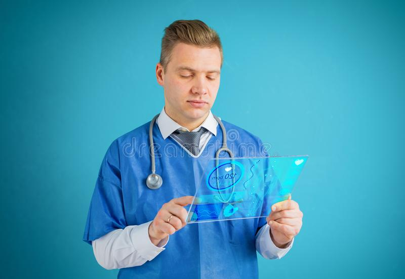 Doctor using futuristic glass tablet computer stock photography
