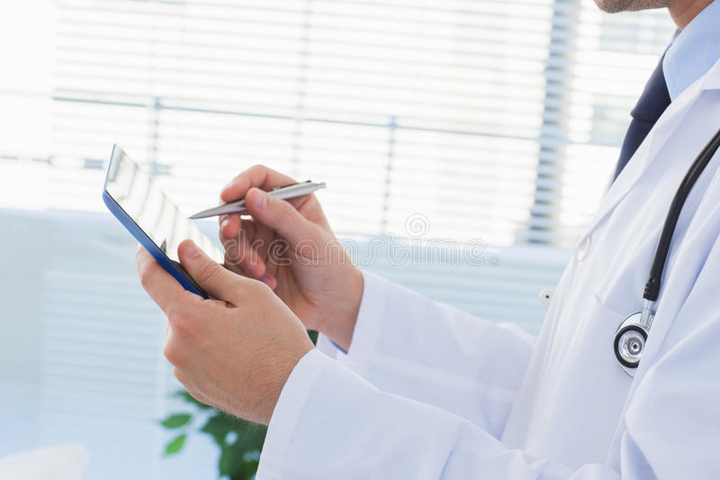 Download Doctor using his tablet pc stock image. Image of smiling - 33052341