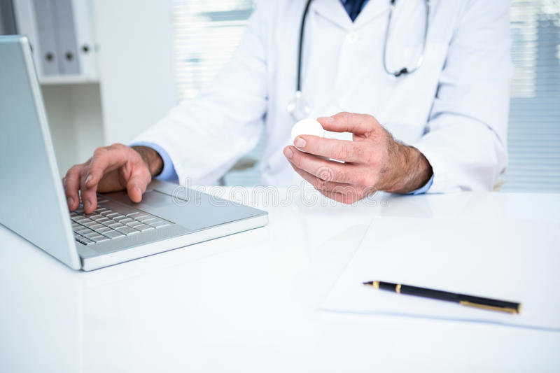 Doctor using laptop at clinic. Midsection of doctor using laptop at clinic stock photography