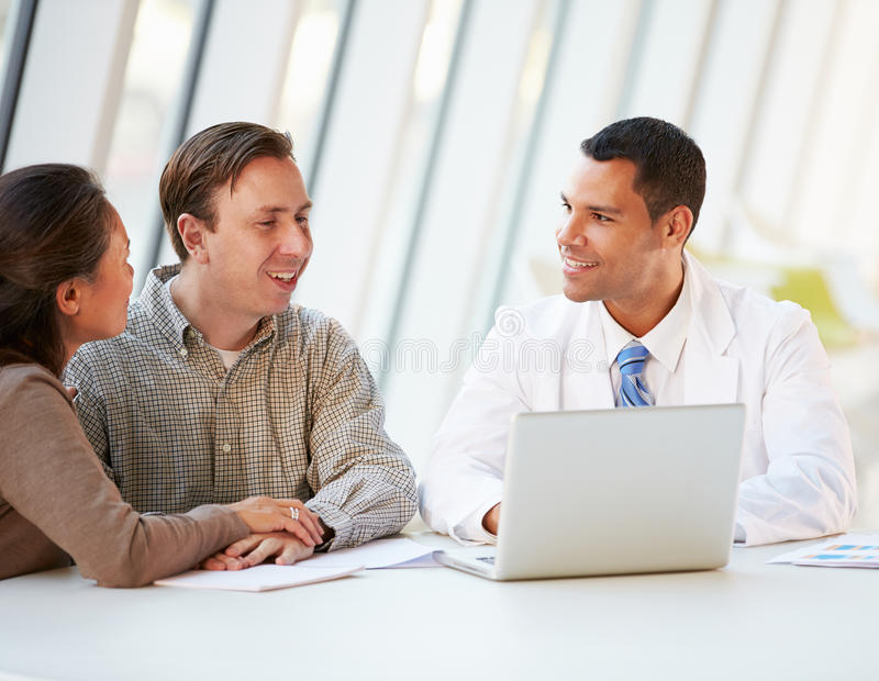 Doctor Using Laptop Discussing Treatment With Patients Stock Images