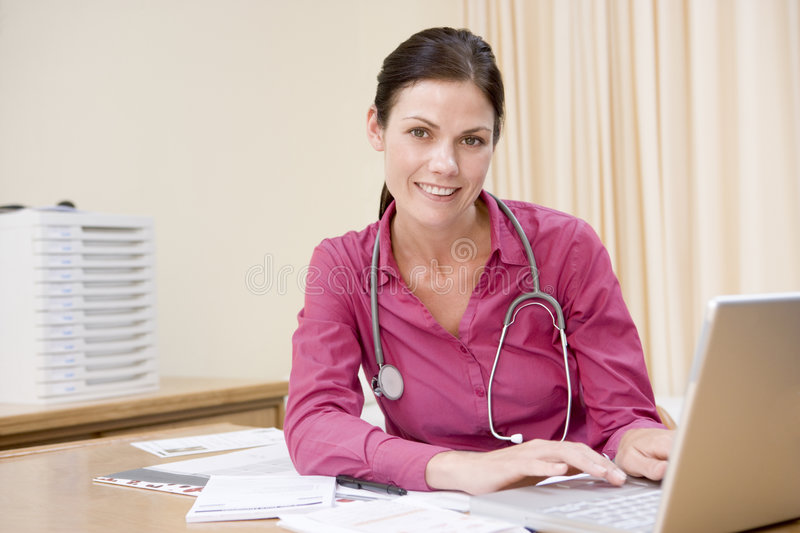 Doctor using laptop in doctor's office smiling royalty free stock photos