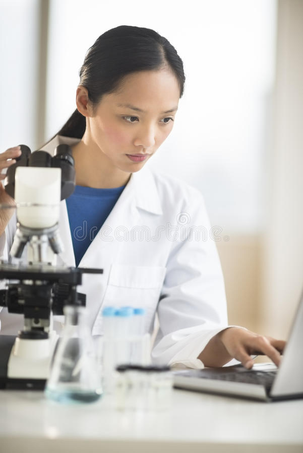 Doctor Using Laptop With Microscope At Desk stock image