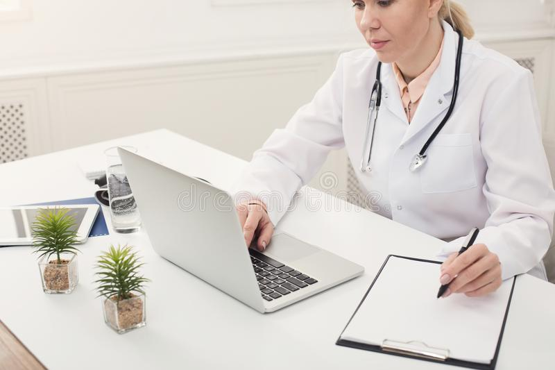 Doctor using laptop and writing notes at office royalty free stock photo