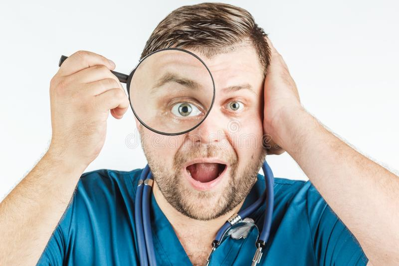 Doctor using a magnifying glass on a white background. stock photography