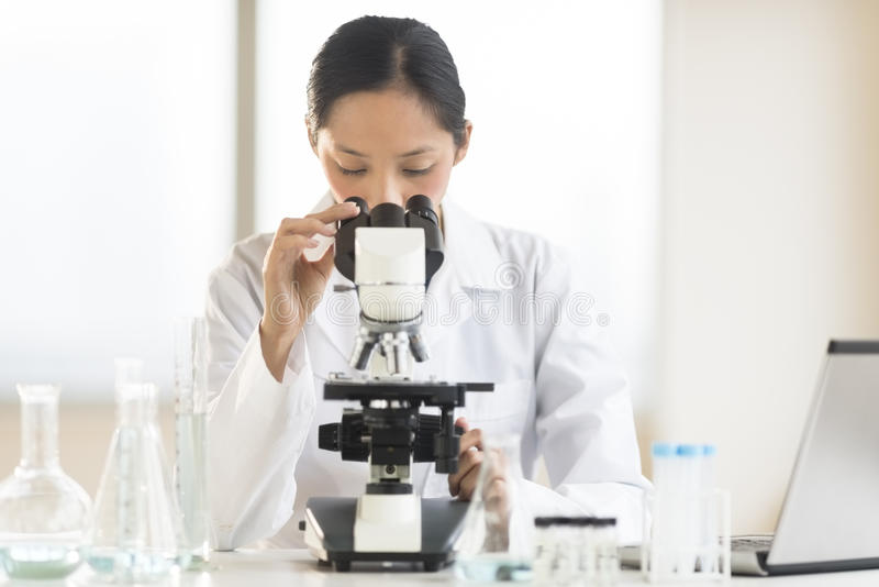 Doctor Using Microscope At Desk In Laboratory. Mid adult Asian female doctor using microscope at desk in laboratory stock photography