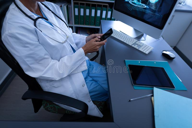 Doctor using mobile phone in clinic at hospital. High angle view of Caucasian female doctor using mobile phone in clinic at hospital royalty free stock image