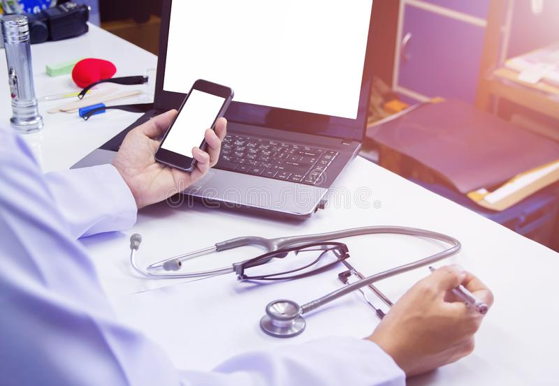 Doctor using mobile phone reading report Cancer Treatment on desk with sunset light. Selective focus stock photography