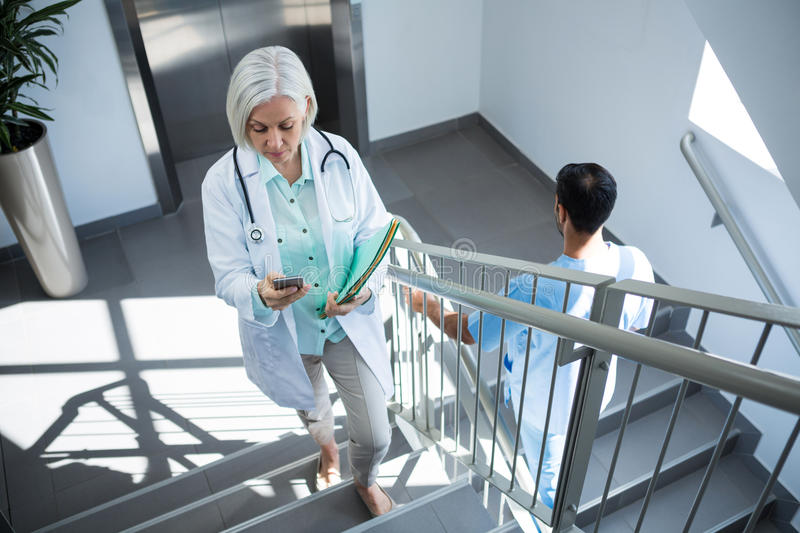 Doctor using mobile phone while walking on staircase. In hospital royalty free stock photography