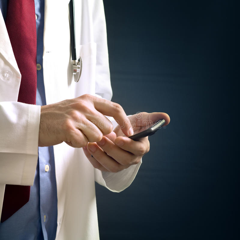 Doctor using smartphone device. Male doctor in white coat is using a modern smartphone device with tocuh screen stock photography