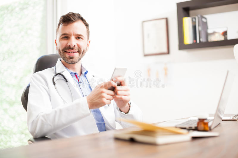 Doctor using social media on a smartphone. Handsome Hispanic young doctor updating his social media status on his smartphone while working in his office stock images
