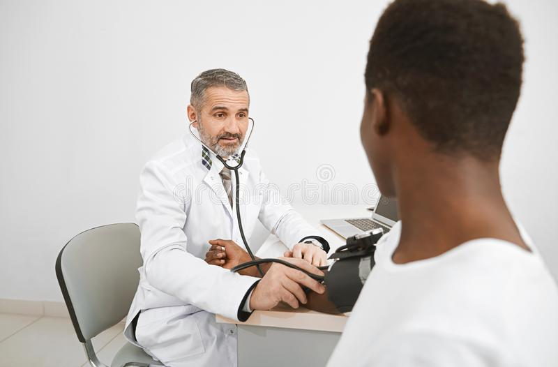 Doctor measuring blood pressure with sphygmomanometer. Doctor using sphygmomanometer for measuring blood pressure of patient. African men sitting on stock image