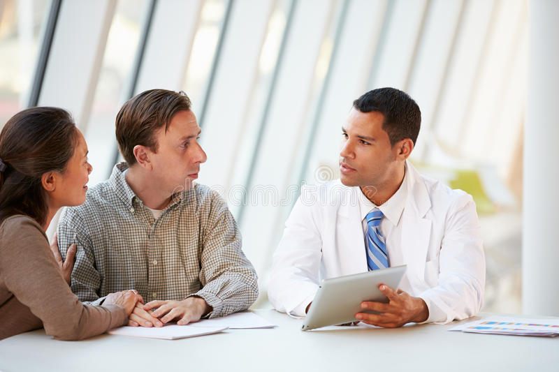 Doctor Using Tablet Computer Discussing Treatment With Patients. Indoors stock image