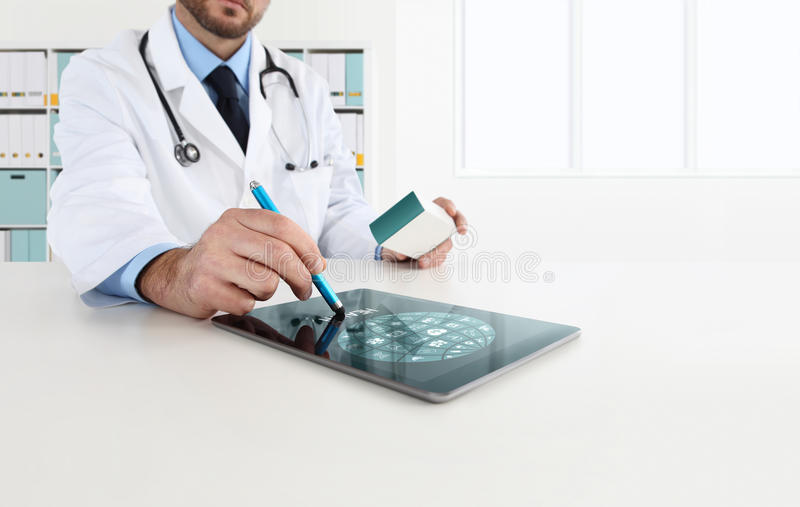 Doctor using tablet on desk prescribes medicine. Doctor using tablet on desk prescribes the medicine royalty free stock image