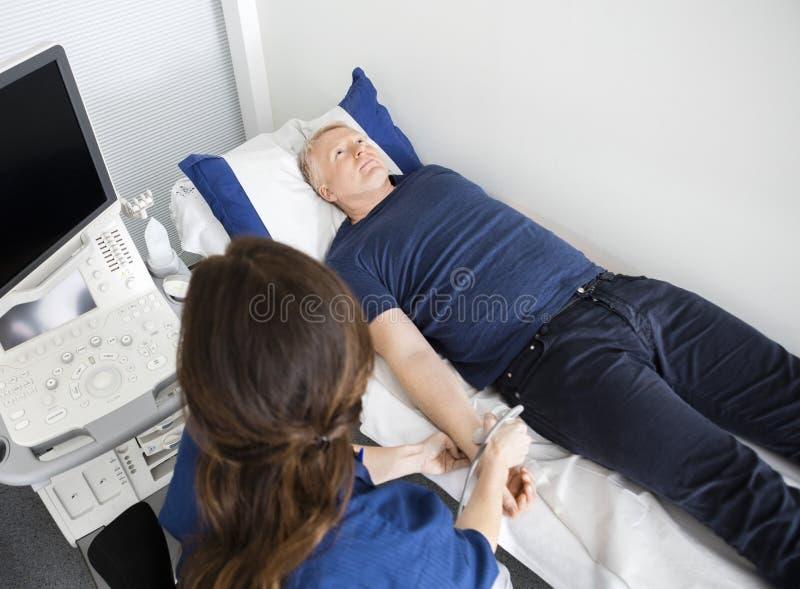 Doctor a Using Ultrasound Probe en la muñeca masculina del ` s en hospital imagen de archivo