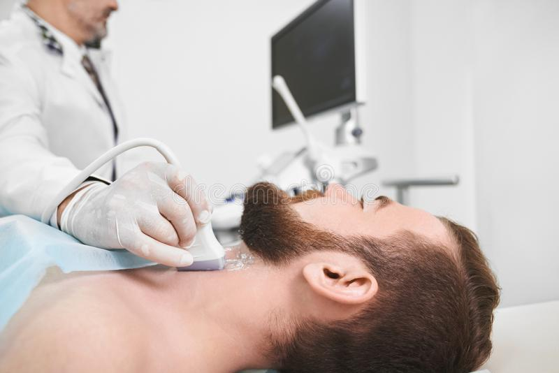 Doctor using ultrasound probe for lymph node diagnosis. stock photo