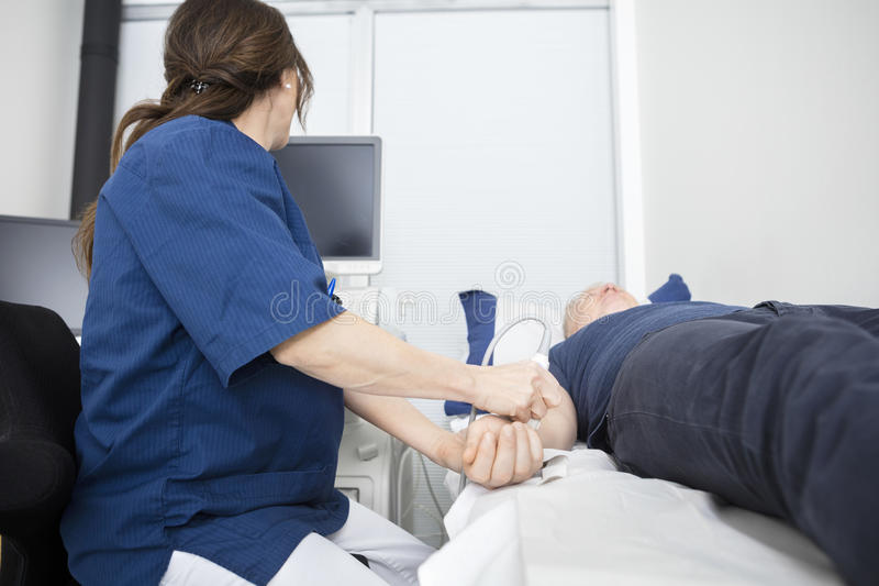 Doctor Using Ultrasound Probe On Male`s Hand In Hospital. Female doctor using ultrasound probe on mature male`s hand while looking at monitor in hospital stock photo