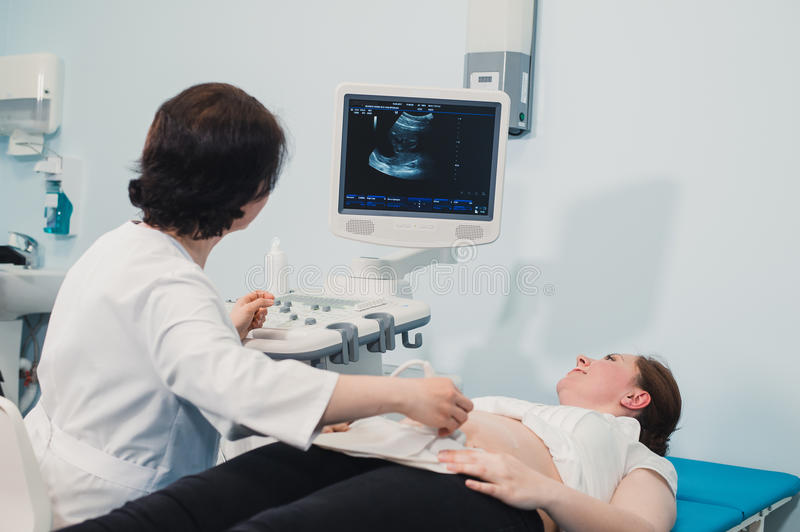 Doctor using ultrasound and screening stomach of pregnant woman. Doctor using ultrasound and screening stomach of pregnant woman royalty free stock image