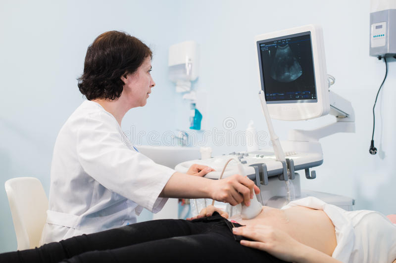 Doctor using ultrasound and screening stomach of pregnant woman. Doctor using ultrasound and screening stomach of pregnant woman stock photo