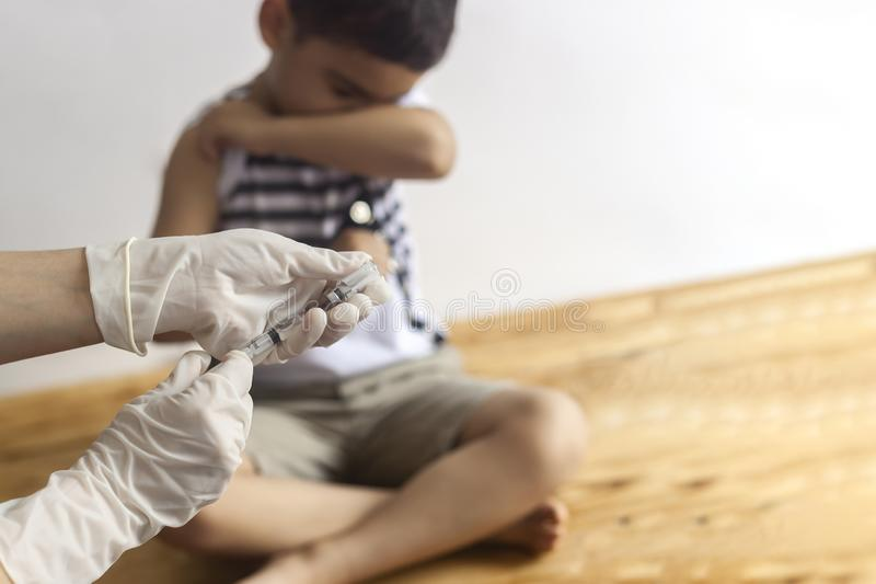 A doctor vaccinating young patient. Little boy scared of injection. Child`s Immunization, Children`s Vaccination, Health concept. Ion stock image
