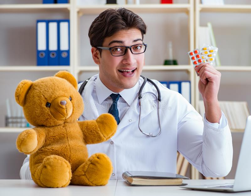 Doctor veterinary pediatrician holding an examination in the off. Ice with a teddy bear stock image