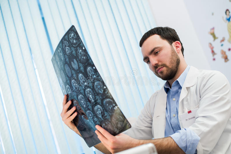 Doctor viewing mri x-ray of brain in office stock photography