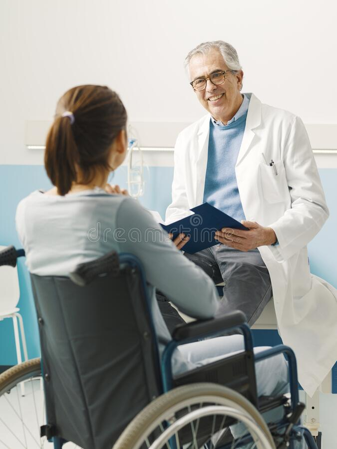 Doctor visiting a paraplegic patient at the hospital royalty free stock photos