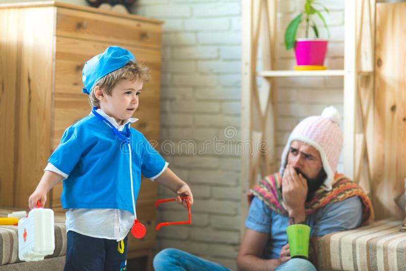 Doctor visiting patient at home. Kid dressed as emergency medical specialist. Father and son playing clinic, healthcare. Concept stock image
