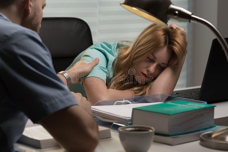 Doctor waking up nurse. Image of doctor waking up nurse sleeping on desk royalty free stock photo