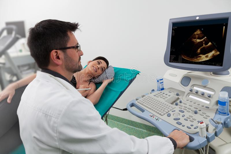 Doctor watching the medical computer with a woman patient. A dark hair doctor listening to his female patient with a ultrasound ecography in a medical room using stock photos