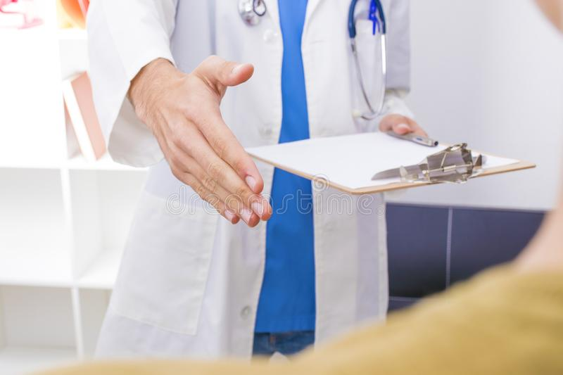 Doctor waving with the extended hand stock image