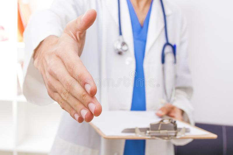 Doctor waving with the extended hand stock photography