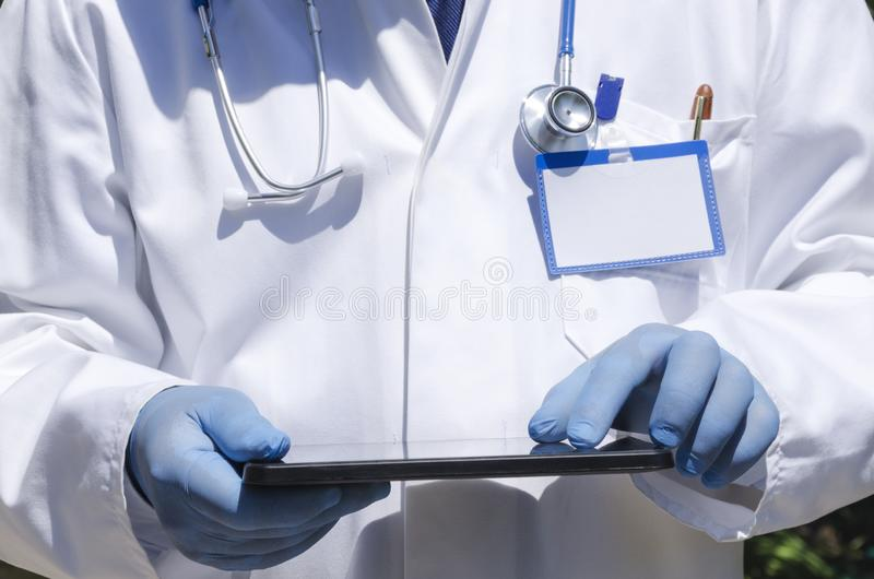 Gardiologist using devise during his work.Vertical shot.Doctor wearing white coat,holding tablet and using it. Doctor wearing laboratory coat and using tablet royalty free stock images