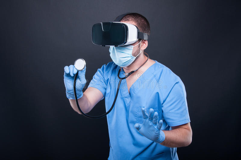 Doctor wearing scrubs using virtual reality glasses and stethoscope stock image